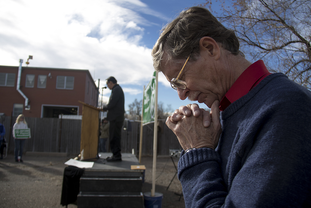 "Pro-life activist Tom Uebbing bows his head as Father John Paul Leyba leads a prayer. A ""Defund Planned Parenthood"" Rally outside Planned Parenthood of the Rockies, Feb. 11, 2017. (Kevin J. Beaty/Denverite)  abortion; pro life; planned parenthood; denver; colorado; kevinjbeaty; denverite; copolitics; politics;"