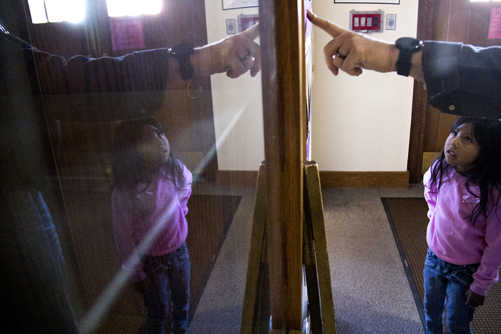 Jeanette Vizguerra's daughter Zury looks at a board of First Unitatian Society leaders with church admin Glenn Barrows. Feb. 15, 2017. (Kevin J. Beaty/Denverite)  jeanette vizguerra; immigration; undocumented; deportation; sanctuary; denver; colorado; kevinjbeaty; denverite;