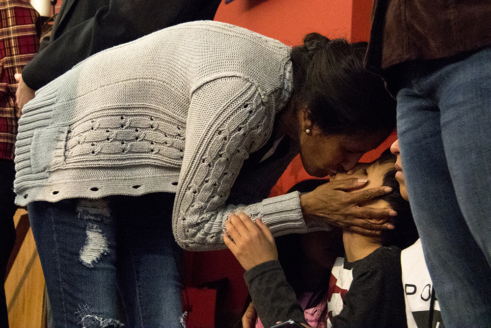 Jeanette Vizguerra kisses her son Roberto on stage at the First Unitarian Society of Denver, where she and her family addressed supporters and the press after she announced she would take sanctuary here to avoid deportation, Feb. 15, 2017. (Kevin J. Beaty/Denverite)  jeanette vizguerra; immigration; undocumented; deportation; sanctuary; denver; colorado; kevinjbeaty; denverite;