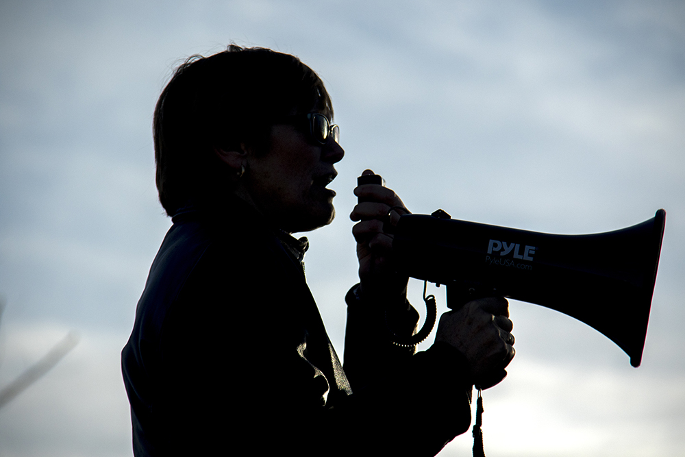 Jeanette Baust speaks at a rally outside of the GEO private immigrant detention facility. (Kevin J. Beaty/Denverite)  ICE; immigration; deportation; aurora; protest; rally; denver; colorado; kevinjbeaty; denverite