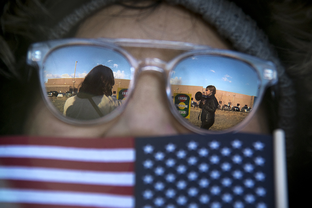 Misun Oh holds a tiny flag at a rally outside of the GEO private immigrant detention facility. (Kevin J. Beaty/Denverite)  ICE; immigration; deportation; aurora; protest; rally; denver; colorado; kevinjbeaty; denverite