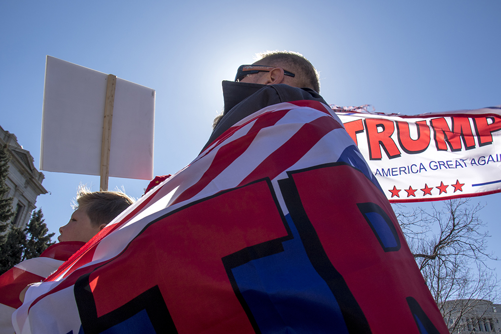 Albert Keller strands with his son Gavin, both draped in flags. A rally in support of President Trump, Feb. 27, 2017. (Kevin J. Beaty/Denverite)  copolitics; politics; trump; rally; protest; capitol; denver; colorado; denverite; kevinjbeaty