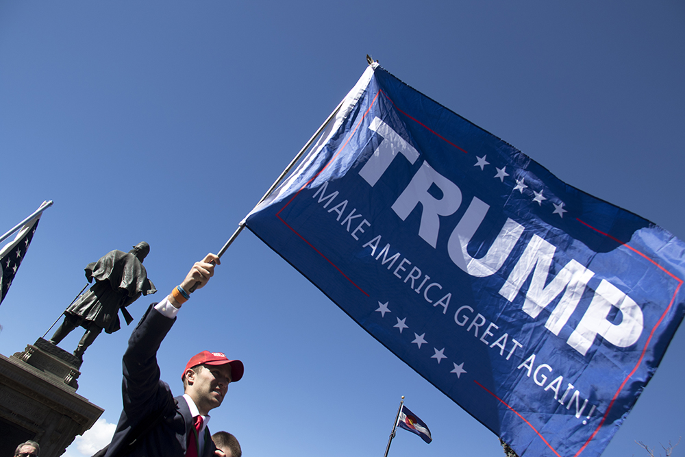 Denverite Alex Inscoe holds a flag at a rally in support of President Trump, Feb. 27, 2017. (Kevin J. Beaty/Denverite)