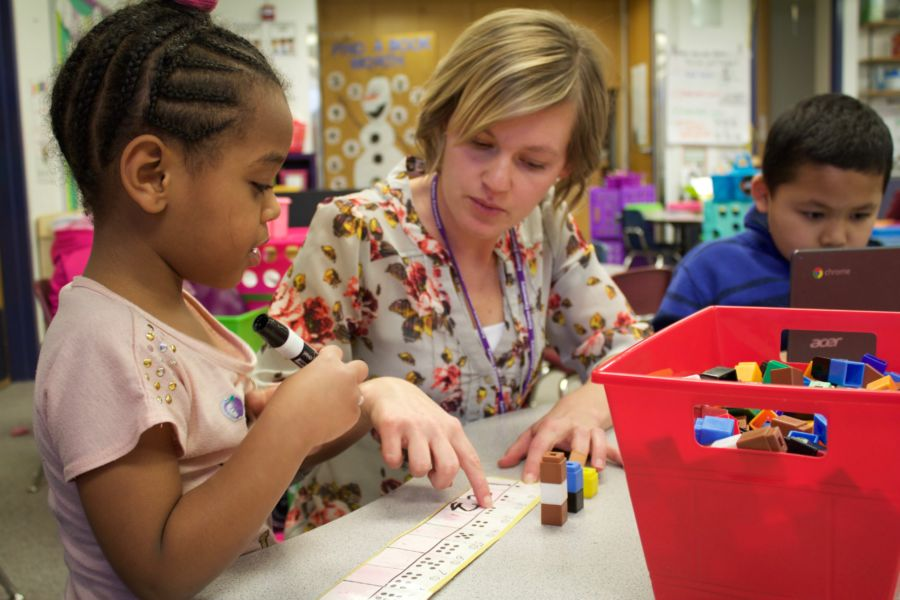 A kindergarten teacher at Kenton Elementary in Aurora helps a student practice saying and writing numbers on a Thursday afternoon in February. (Yesenia Robles/Chalkbeat)