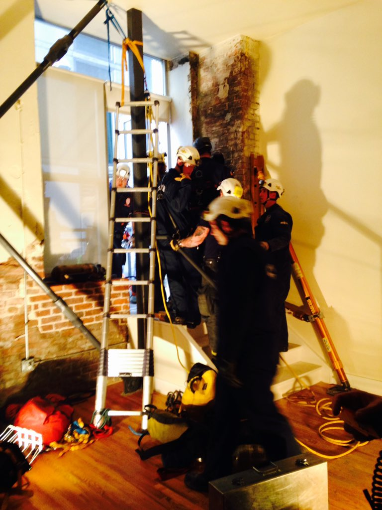 Emergency responders address a man trapped in a chimney. (Denver Fire Department)
