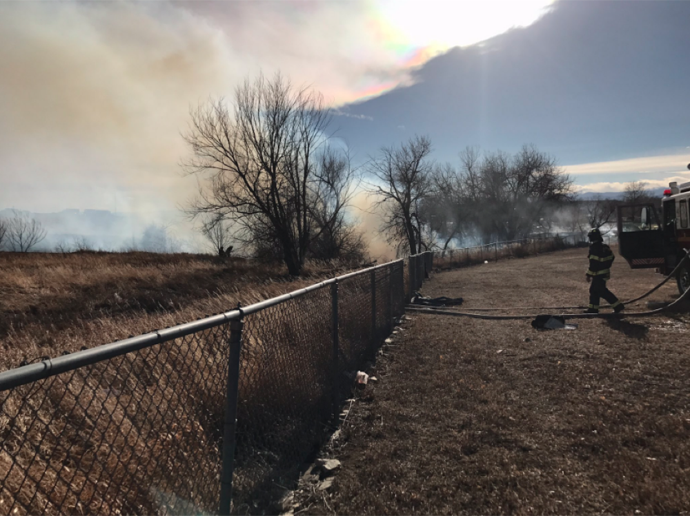 Firefighters take on a grass fire near I-25 and Thornton Parkway. (North Metro Fire Rescue District)