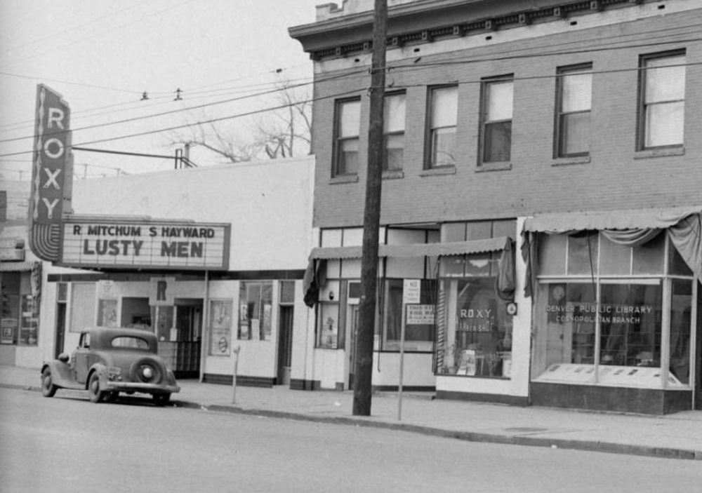 """The Roxy theater on the 2500 block of Welton Street in the Five Points neighborhood of Denver, Colorado. The marquis advertises: """"R Mitchum S Hayward Lusty Men."""" The Denver Public Library Cosmopolitan Branch is on the corner of 26th and Welton Street. (Clarence F. Holmes/Denver Public Library/Western History Collection/X-22314)"""