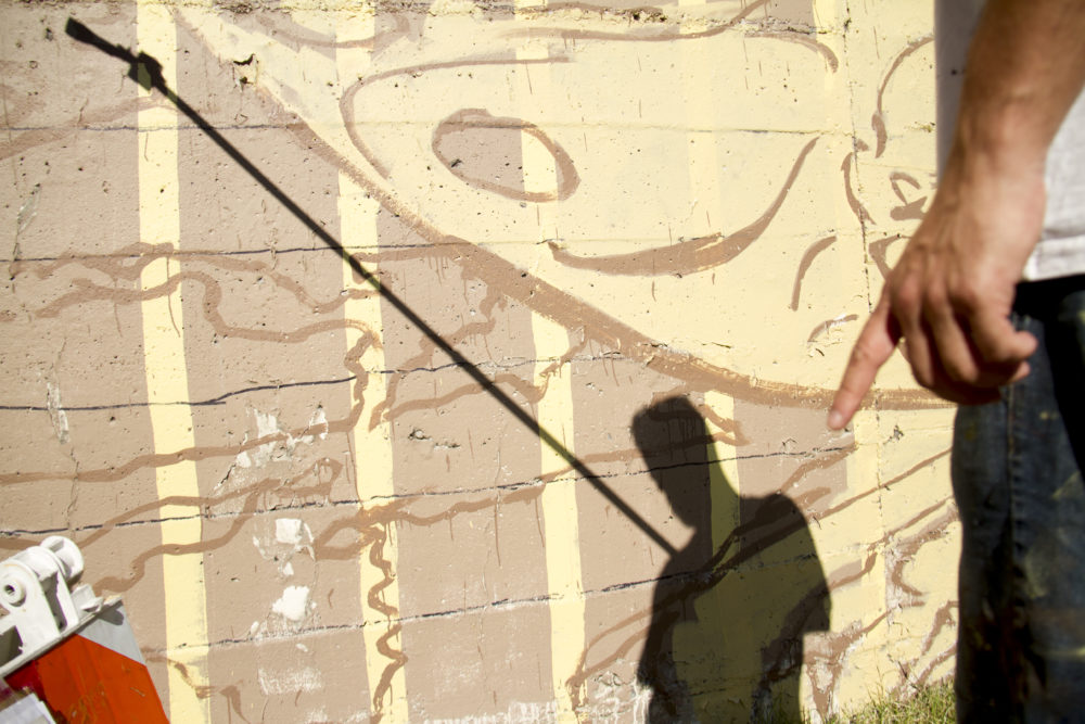 Alexandre Orion works on a mural along the Cherry Creek Trail, Sept. 16, 2017. (Kevin J. Beaty/Denverite)  public art; cherry creek trail; mural; alexandre orion; kevinjbeaty; denver; colorado; denverite;