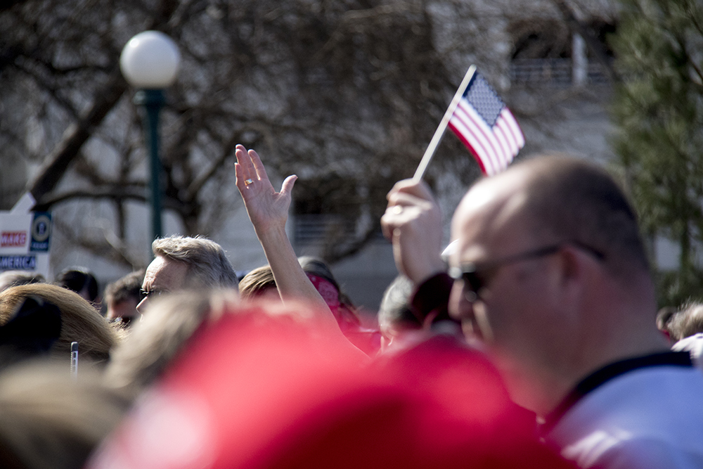 Someone raises a hand during the opening prayer. A pro-Trump rally that was opposed by a group of anarchist protesters, Mar. 4, 2017. (Kevin J. Beaty/Denverite)  protest; rally; copolitics; kevinjbeaty; denver; colorado; denverite; capitol hill;
