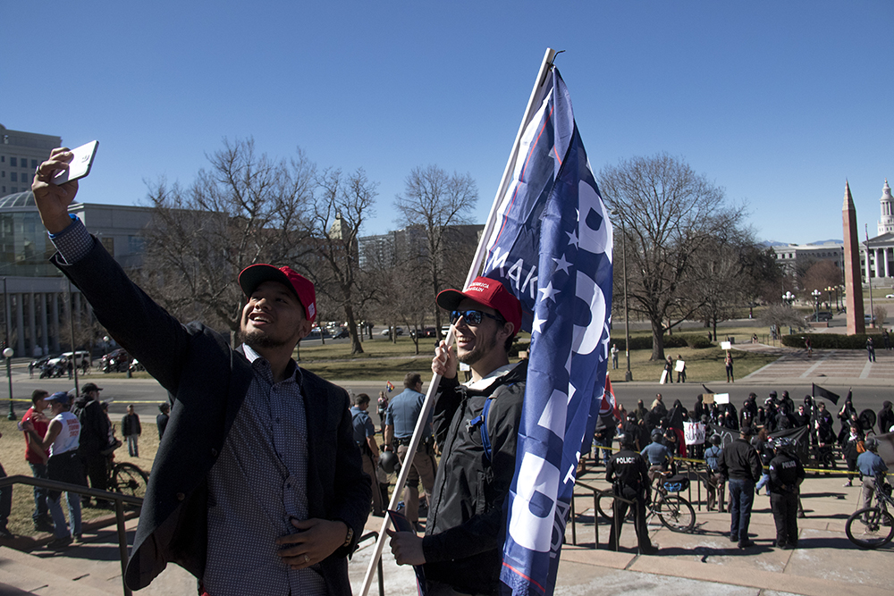 Richard Trujillo and a man named Dylan take selfies in front of opposing protesters. A pro-Trump rally that was opposed by a group of anarchist protesters, Mar. 4, 2017. (Kevin J. Beaty/Denverite)  protest; rally; copolitics; kevinjbeaty; denver; colorado; denverite; capitol hill;