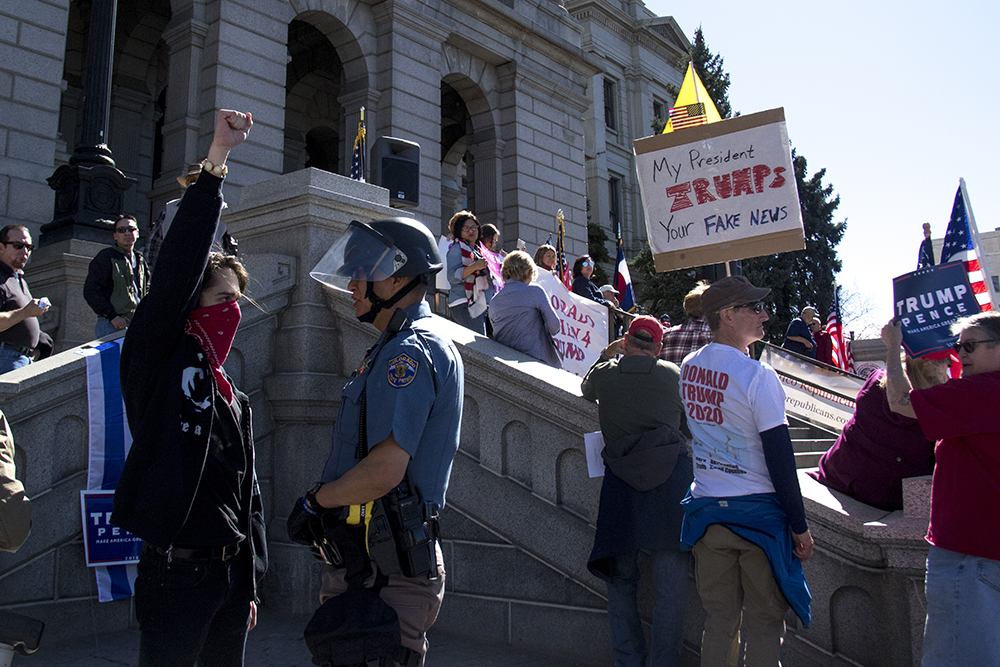 Anti-Trump protester Cooper Carrington holds a fist up to a State Trooper. A pro-Trump rally that was opposed by a group of anarchist protesters, Mar. 4, 2017. (Kevin J. Beaty/Denverite)  protest; rally; copolitics; kevinjbeaty; denver; colorado; denverite; capitol hill;