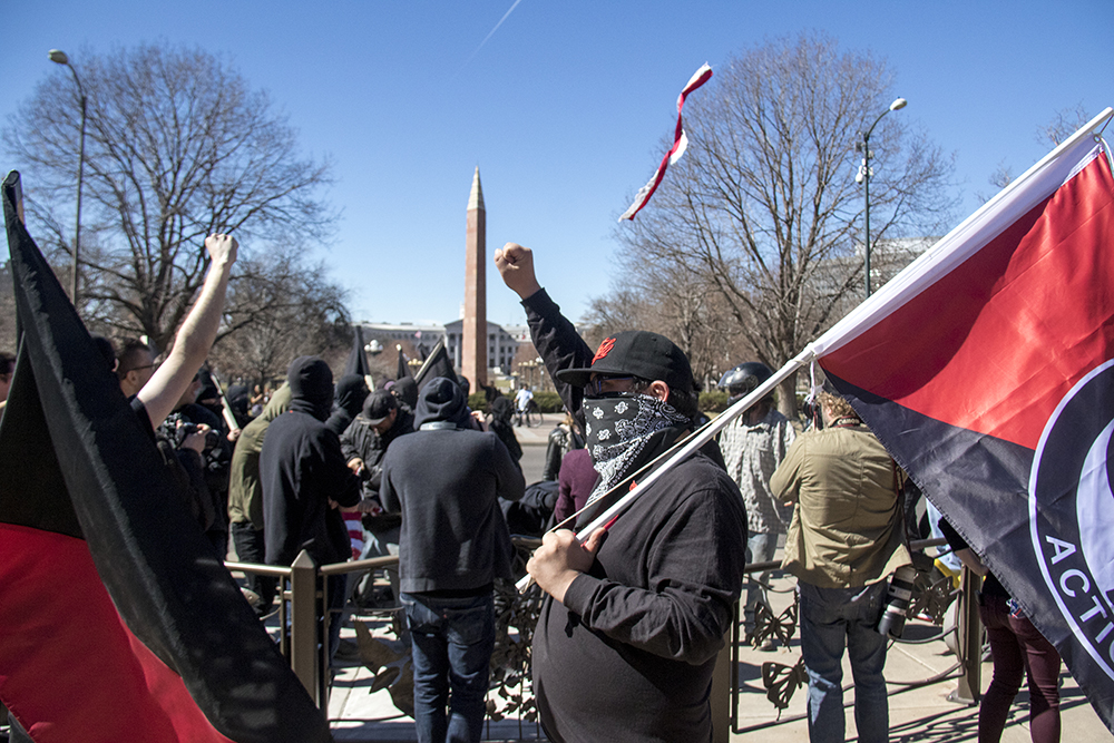 Anarchists raise fists and tear flags. A pro-Trump rally that was opposed by a group of anarchist protesters, Mar. 4, 2017. (Kevin J. Beaty/Denverite)  protest; rally; copolitics; kevinjbeaty; denver; colorado; denverite; capitol hill;