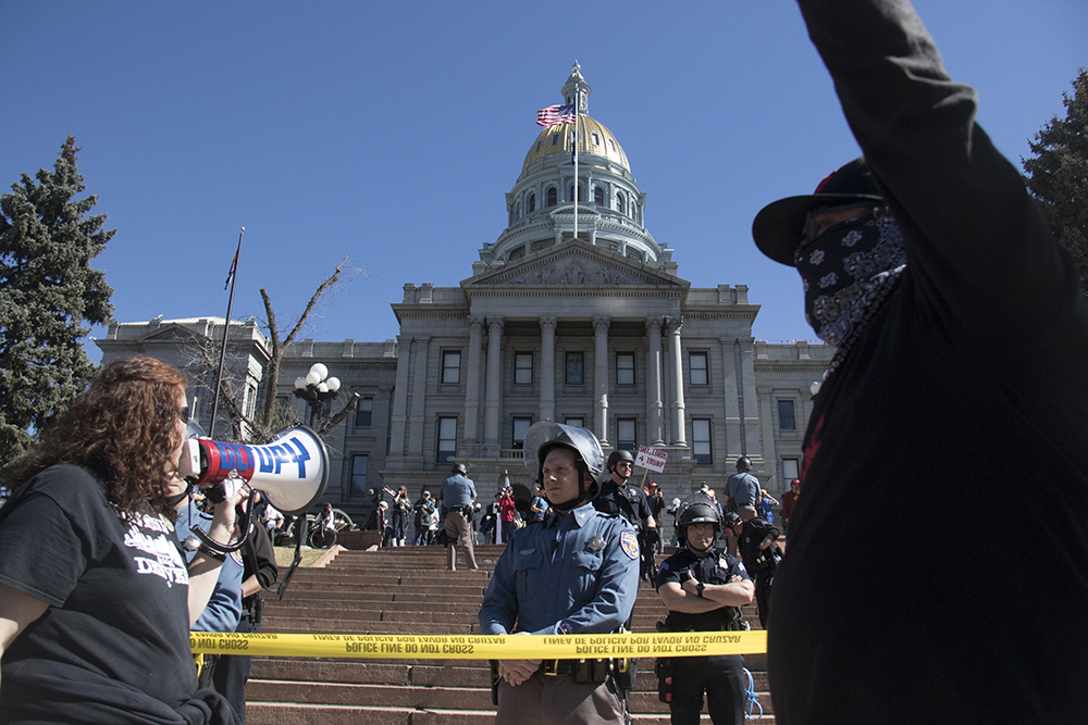 Caryn Sodaro leads the anarchist rally with a bull horn. Law enforcement officers stand between pro-Trump ralliers and group of anarchist protesters, Mar. 4, 2017. (Kevin J. Beaty/Denverite)  protest; rally; copolitics; kevinjbeaty; denver; colorado; denverite; capitol hill;