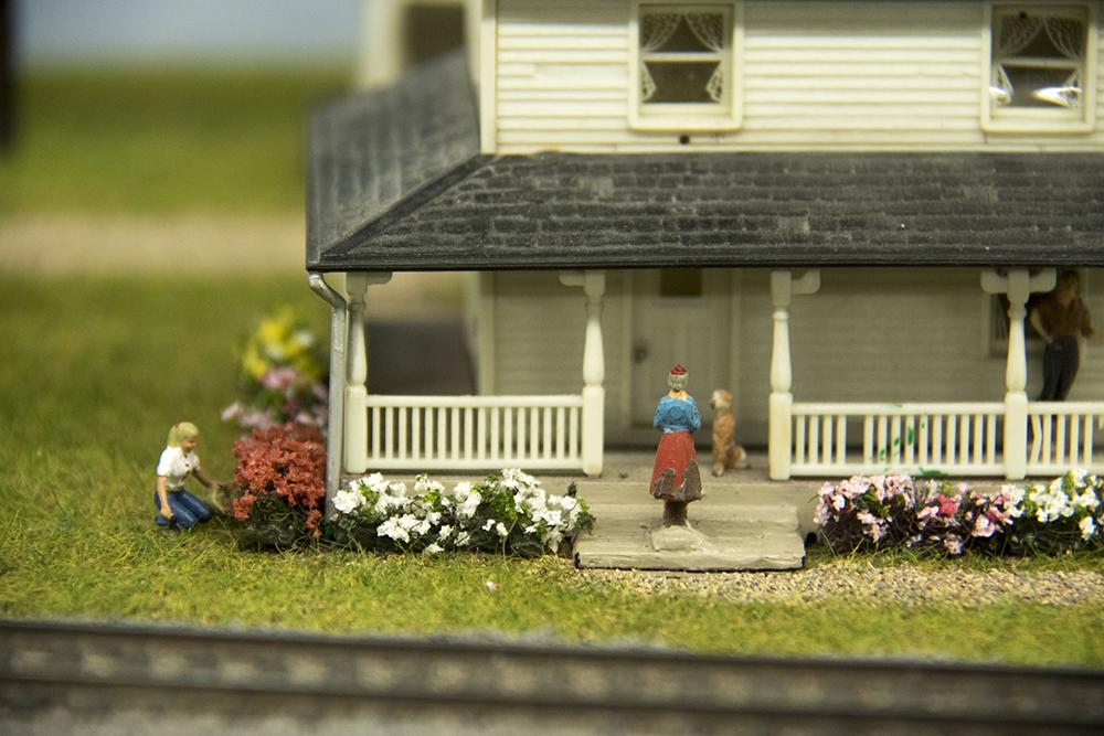 A tiny lady picks tiny flowers. The Rocky Mountain Toy Train Show, Mar. 4, 2017. (Kevin J. Beaty/Denverite)  hobby; toy train; model train; toys; kevinjbeaty; denver mart; rocky mountain toy train show; colorado; denver; denverite;