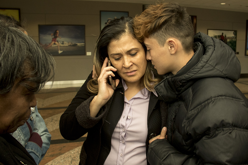 Erica Rodriguez is comforted by her son Angel as she speaks to her husband Isidro before he is taken to the GEO private immigration detention facility in Aurora. DIA, Mar. 6, 2017. (Kevin J. Beaty/Denverite)  denver; colorado; denverite; kevinjbeaty; immigration; isidro quintana; dia;