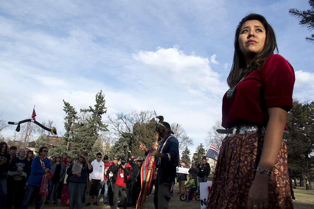 Joi Lynch stands in sunlight as Robert Cross speaks to the crowd. A rally against the Dakota Access Pipeline, March 10, 2017. (Kevin J. Beaty/Denverite)  march; protest; rally; sunken gardens; capitol; indigenous; native american; nodapl; dakota access pipeline; standing rock; kevinjbeaty; denver; denverite; colorado;