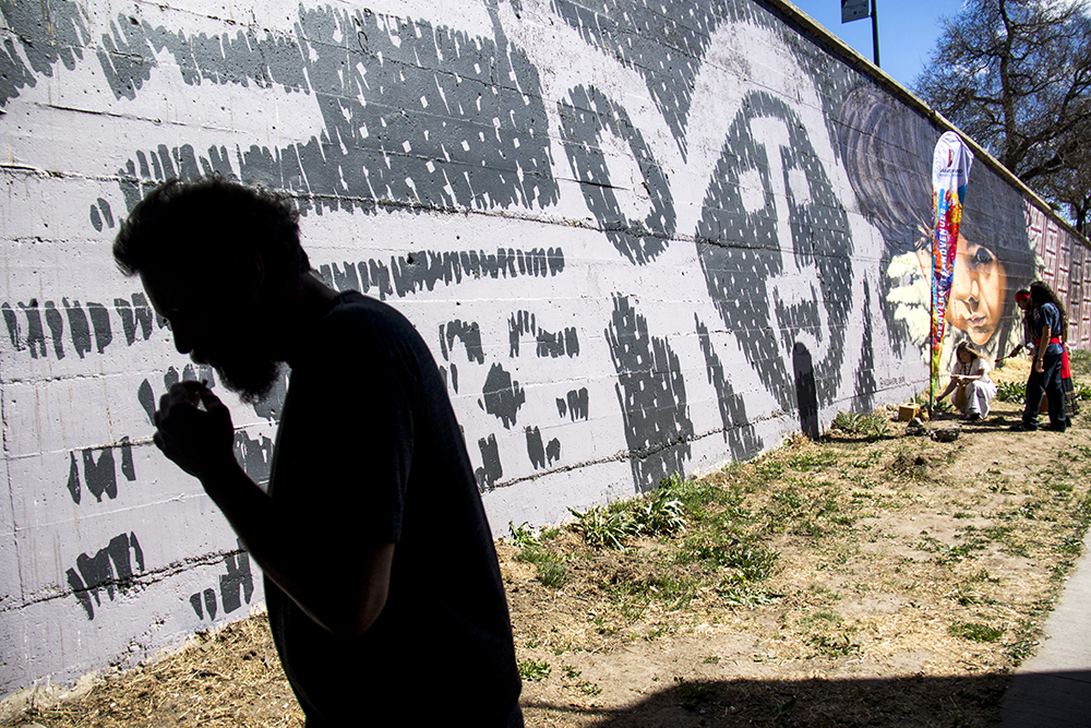 Brazilian artist Alexandre Orion and his mural on the Cherry Creek Trail during a ceremony re-introducing it after it was vandalized this winter, March 23, 2017. (Kevin J. Beaty/Denverite)  public art; cherry creek trail; Alexandre Orion; kevinjbeaty; denverite; denver; colorado;