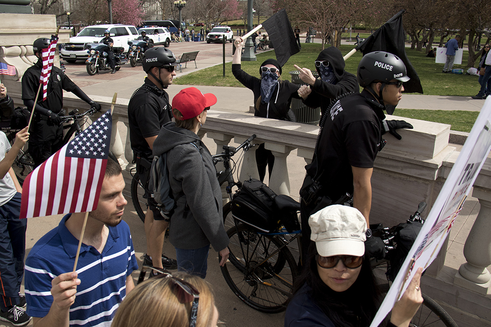 """Anarchist activists yell obsenities at marching Trump supporters. A """"Make America Great Again"""" rally at Civic Center Park, March 25, 2017. (Kevin J. Beaty/Denverite)  protest; rally; kevinjbeaty; denverite; denver; colorado; civic center park; copolitics;"""