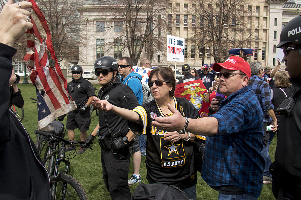 """Kenneth Cawood reaches for a charred flag over a police line. A """"Make America Great Again"""" rally at Civic Center Park, March 25, 2017. (Kevin J. Beaty/Denverite)  protest; rally; kevinjbeaty; denverite; denver; colorado; civic center park; copolitics;"""