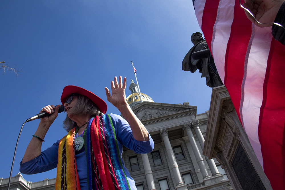 """Georgann Low leads the crowd in """"America The Beautiful."""" A rally at the Capitol on the """"day without women,"""" Mar. 8, 2017. (Kevin J. Beaty/Denverite)  womens march; day without women; protest; capitol; rally; kevinjbeaty; denver; denverite; colorado;"""