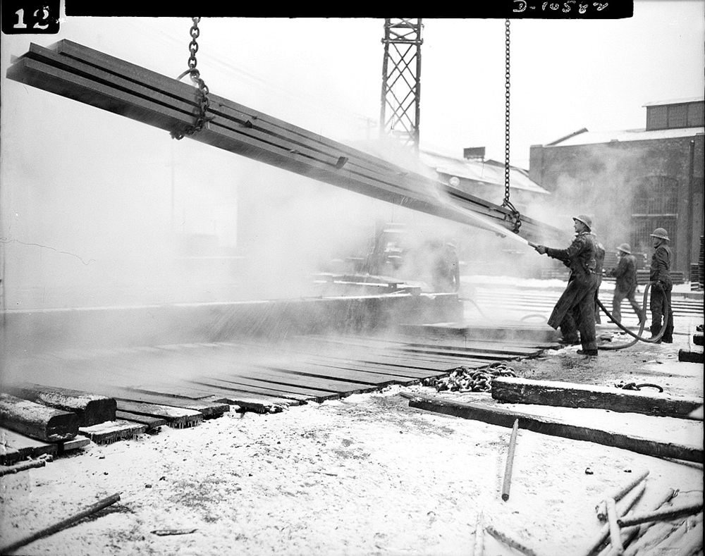 """Denver, Colorado. Workers giving ship steel a thorough rinsing after it has been """"pickled"""" in the highest steel """"pickling"""" vat in the world. The """"pickling"""" operation, giving steel a sulphuric bath to remove mill scale, is a common sight at Seaboard Shipyards, and is something unique at the mile-high Denver fabricating plant and an illustration of American industrial ingenuity, May 1942. (Library of Congress/LC-USE6-D-010582)"""
