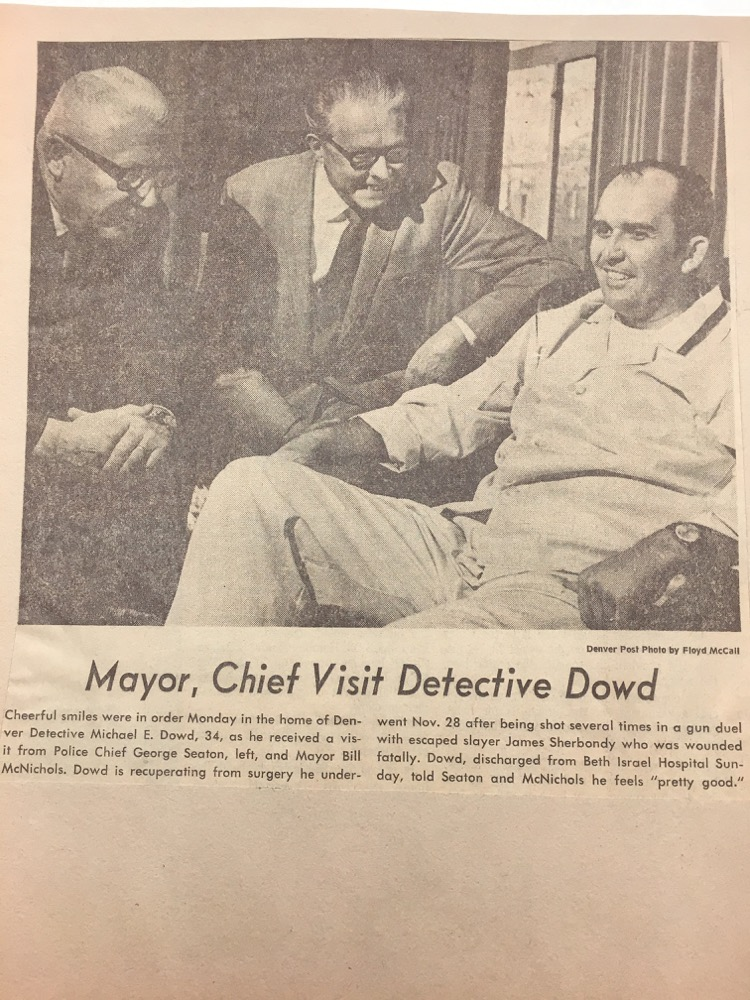 A Denver Post newspaper clipping shows former police chief George Seaton (left) and former mayor Bill McNichols visiting with Michael Dowd.