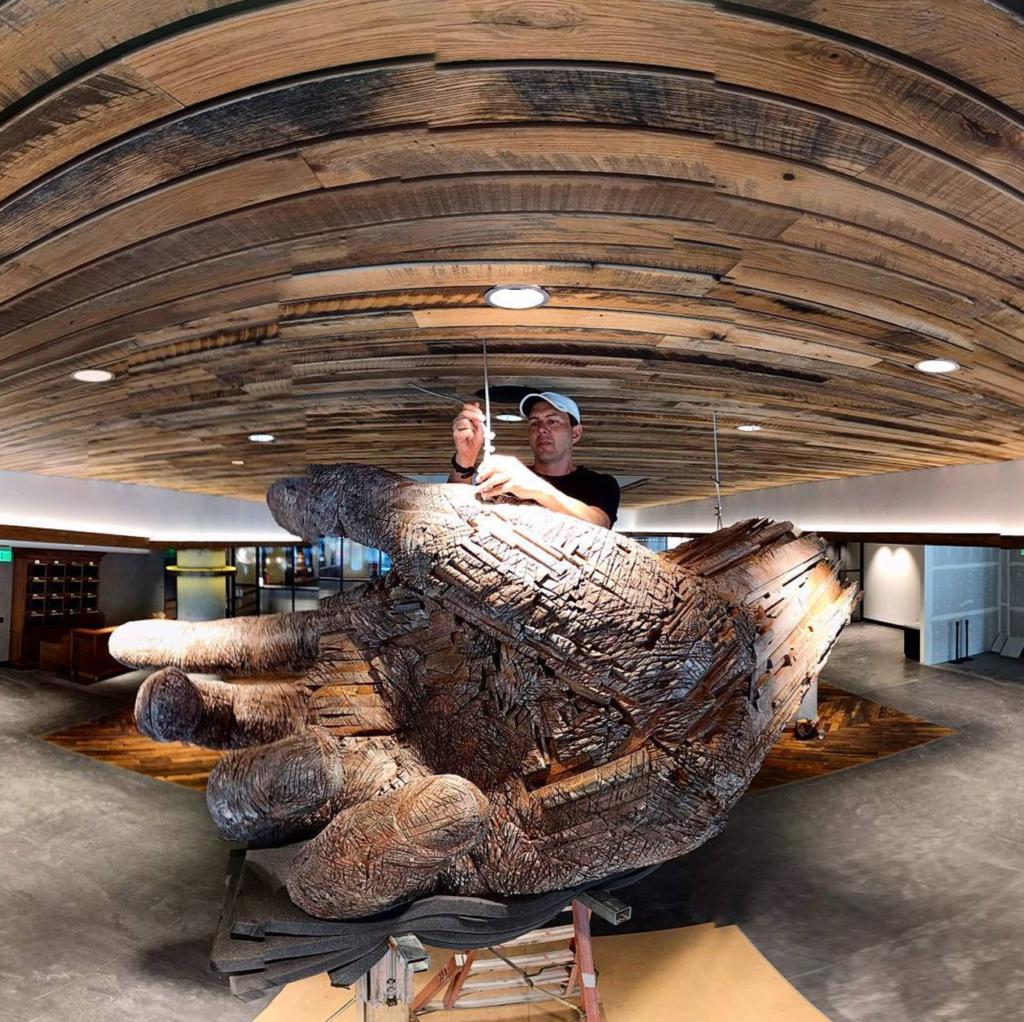 A giant wooden hand and its creator, Colorado artist Andrew Ramiro Tirado. The Dairy Block, Mar. 1, 2017. (Kevin J. Beaty/Denverite)  dairy block; food; the maven hotel; public art; development; construction; ballpark; lodo; denver; colorado; denverite; kevinjbeaty;