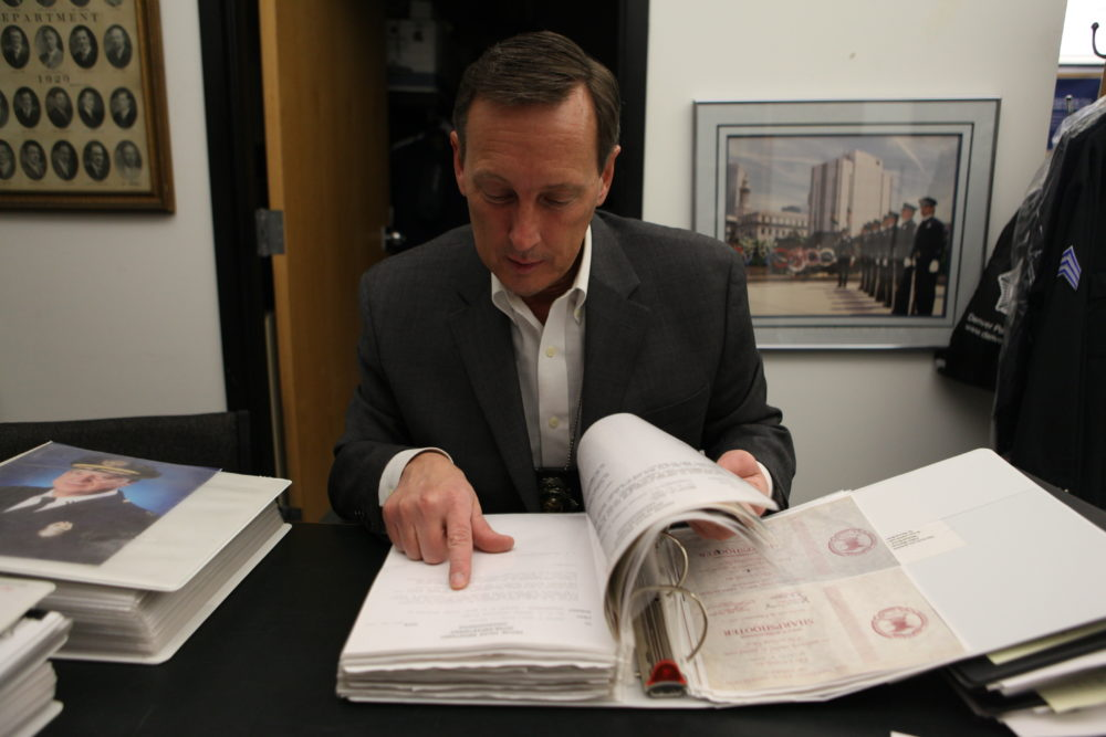Sgt. Dean Christopherson of the Denver Police Department reviews records of Michael Dowd's service. (Andrew Kenney/Denverite)