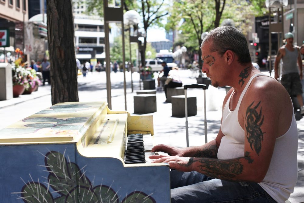 A man plays a painted piano on the 16th Street Mall. (Andrew Kenney/Denverite)