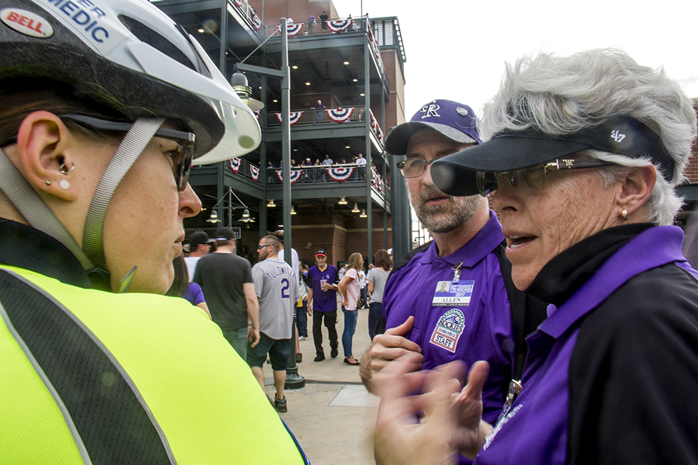 Coors Field staff tells Shae Taylor about a potentially sick customer on opening day, April 8, 2017. (Kevin J. Beaty/Denverite)  emt; denver health; rockies; coors field; denver; denverite; colorado; kevinjbeaty