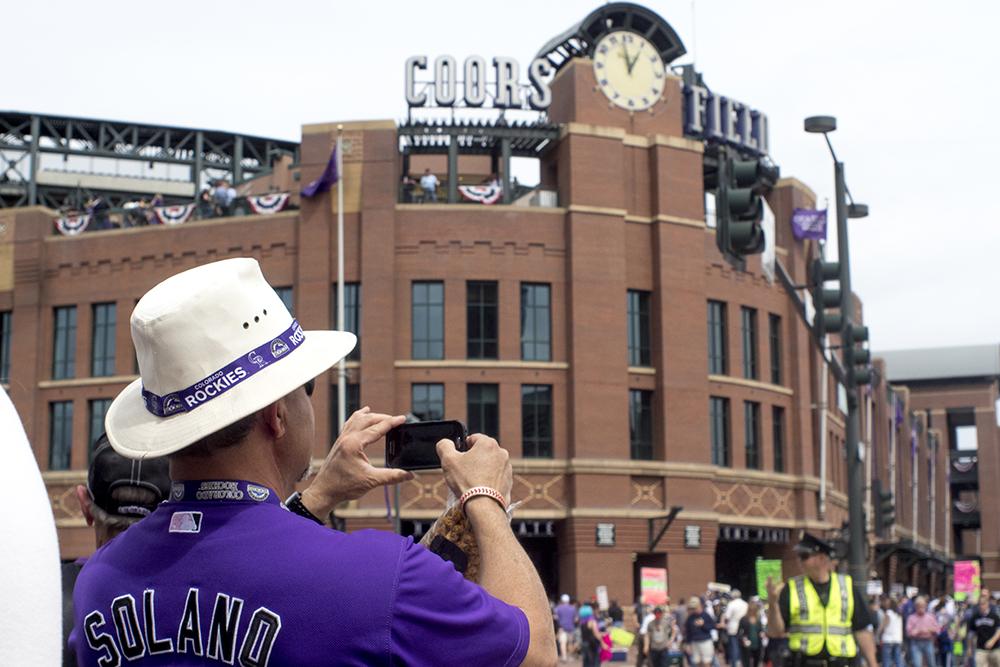 A man takes a photo of Coors Field on opening day, April 7, 2017. (Kevin J. Beaty/Denverite)  rockies; ballpark; coors field; sports; baseball; opening day; denver; colorado; denverite; kevinjbeaty;