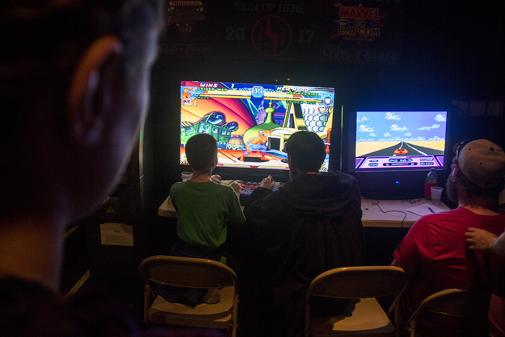 A video game tournament is projected on stage. Nerd Prom at Summit Music Hall, April 8, 2017. (Kevin J. Beaty/Denverite)  nerd prom; cosplay; geek; party; video games; kevinjbeaty; denver; denverite; colorado;