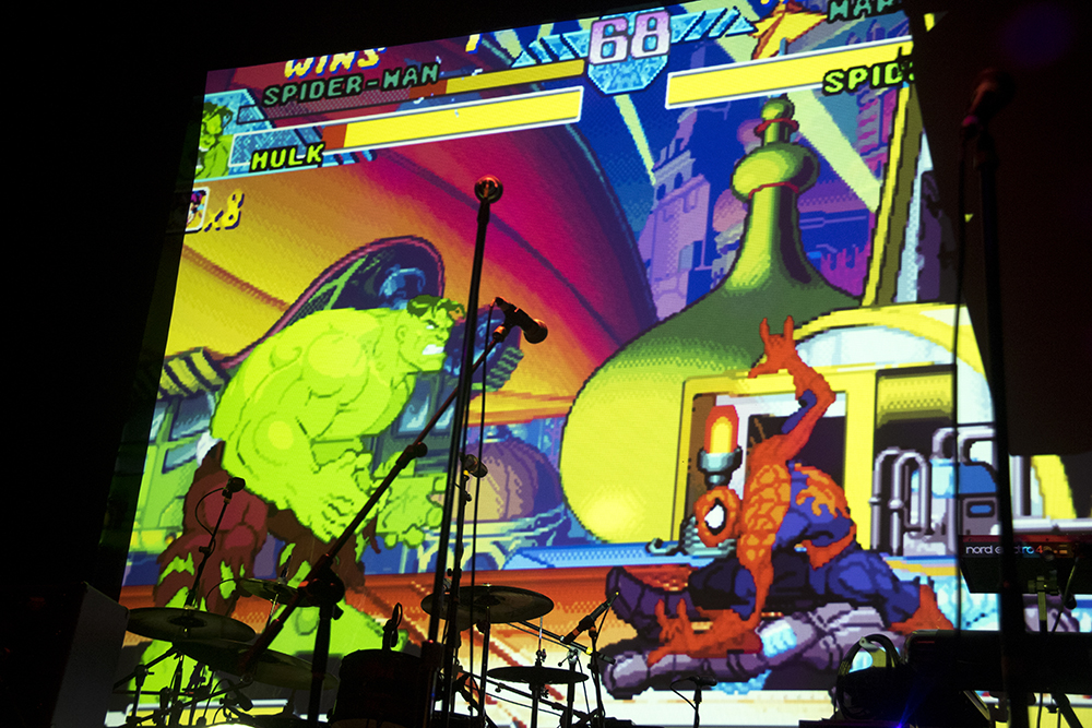 A video game tournament is projected on stage. Nerd Prom at Summit Music Hall, April 8, 2017. (Kevin J. Beaty/Denverite)nerd prom; cosplay; geek; party; video games; kevinjbeaty; denver; denverite; colorado;