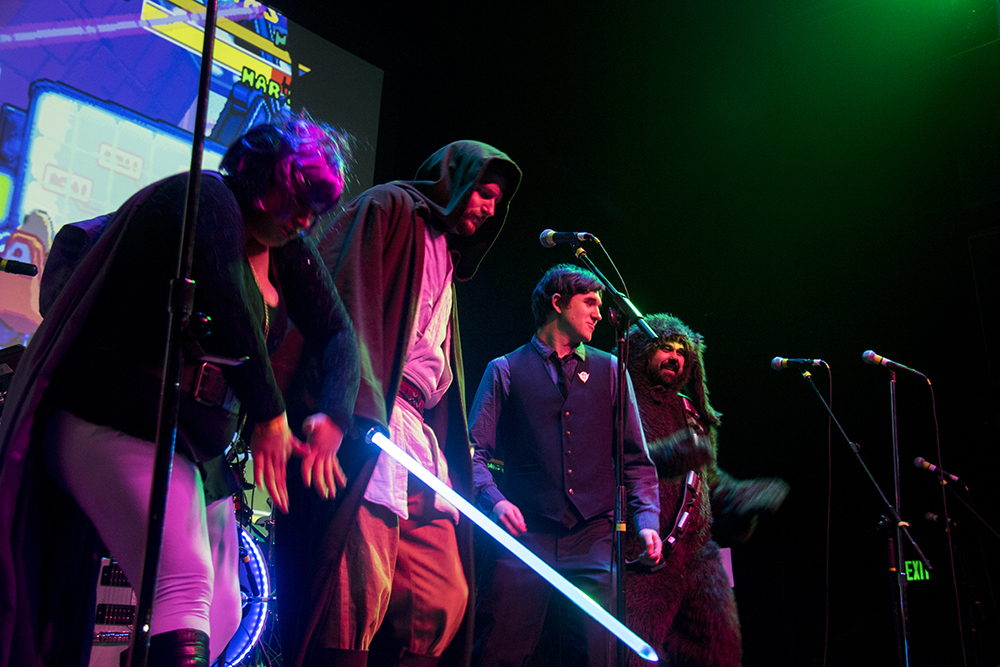 Savanah Overturf as Raven (left to right), Justin Neal as Obi-Wan Kenobi, Alex Miller as Nightwing and Charlie Hanson as Wilfred/Chewbaca get down on stage during a dance contest. Nerd Prom at Summit Music Hall, April 8, 2017. (Kevin J. Beaty/Denverite)  nerd prom; cosplay; geek; party; video games; kevinjbeaty; denver; denverite; colorado;