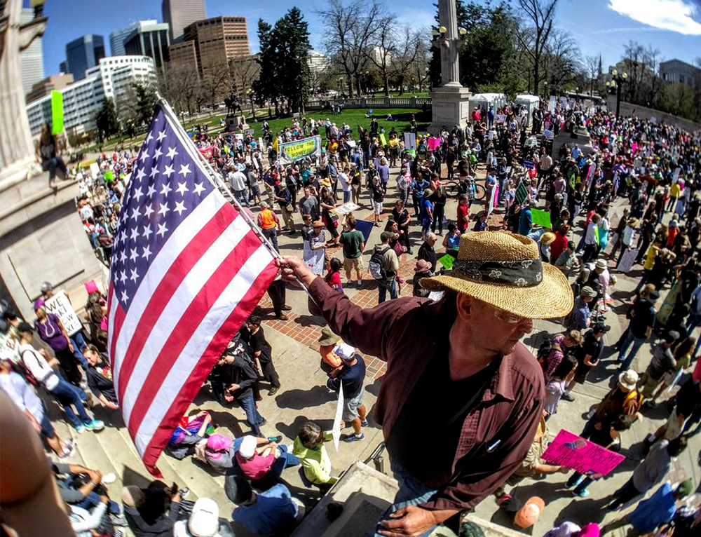 David Reed holds an American Flag over the crowd. The tax day tax march calling for President Trump to release his returns, April 15, 2017. (Kevin J. Beaty/Denverite)  tax day; tax march; protest; copolitics; kevinjbeaty; denver; denverite; colorado; civic center park;