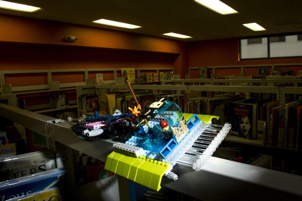 "An intergalactic vessel perched on a bookself at the Rodolfo ""Corky"" Gonzales branch. Denver Public Library LEGO contest. (Kevin J. Beaty/Denverite)  lego; denver public library; toys; kevinjbeaty; denver; colorado; denverite;"