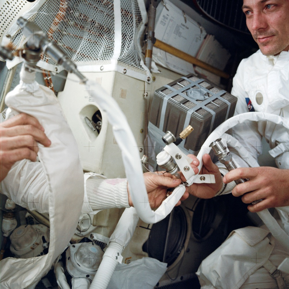 """The late Colorado astronaut John L. Swigert, at right, with the """"mailbox"""" rig improvised to adapt the Command Module's square carbon dioxide scrubber cartridges to fit the Lunar Module, which took a round cartridge. (BASA)"""