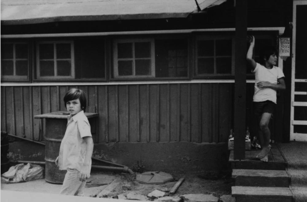 Two boys, identified as Gary and Mike, stand outside a building at Auraria's Camp Malo, south of Evergreen on Turkey Creek Road. (Virginia Castro/Western History and Genealogy Department/Denver Public Library)
