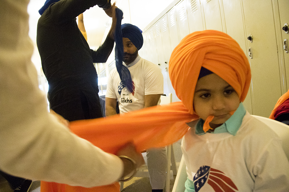 Ramamjit Sandhu and his son Aviraj have turbans wrapped around their heads. The second-annual Sikh festival at East High School, May 28, 2017. (Kevin J. Beaty/Denverite)  sikh; colorado singh sabha; east high school; denver; colorado; parade; kevinjbeaty; denverite;