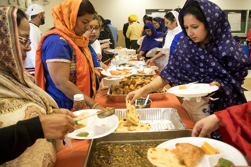 Women wait in line for Indian food. The second-annual Sikh festival at East High School, May 28, 2017. (Kevin J. Beaty/Denverite)  sikh; colorado singh sabha; east high school; denver; colorado; parade; kevinjbeaty; denverite;
