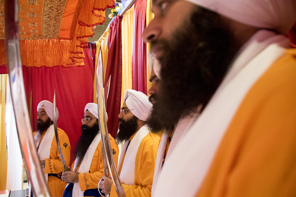 """Men ceremoniously dressed as the Panj Pyare, the """"Five Beloved Ones,"""" or the first Sikhs, stand at the back of an altar in the East High School gym. The second-annual Sikh festival at East High School, May 28, 2017. (Kevin J. Beaty/Denverite)  sikh; colorado singh sabha; east high school; denver; colorado; parade; kevinjbeaty; denverite;"""