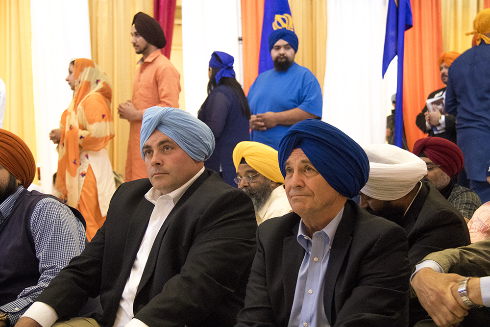 U.S. Representative Ed Perlmutter (right) and Adams County Commissioner Steve O'Dorisio sit in the temple erected inside the East High School gym. The second-annual Sikh festival at East High School, May 28, 2017. (Kevin J. Beaty/Denverite)  sikh; colorado singh sabha; east high school; denver; colorado; parade; kevinjbeaty; denverite;