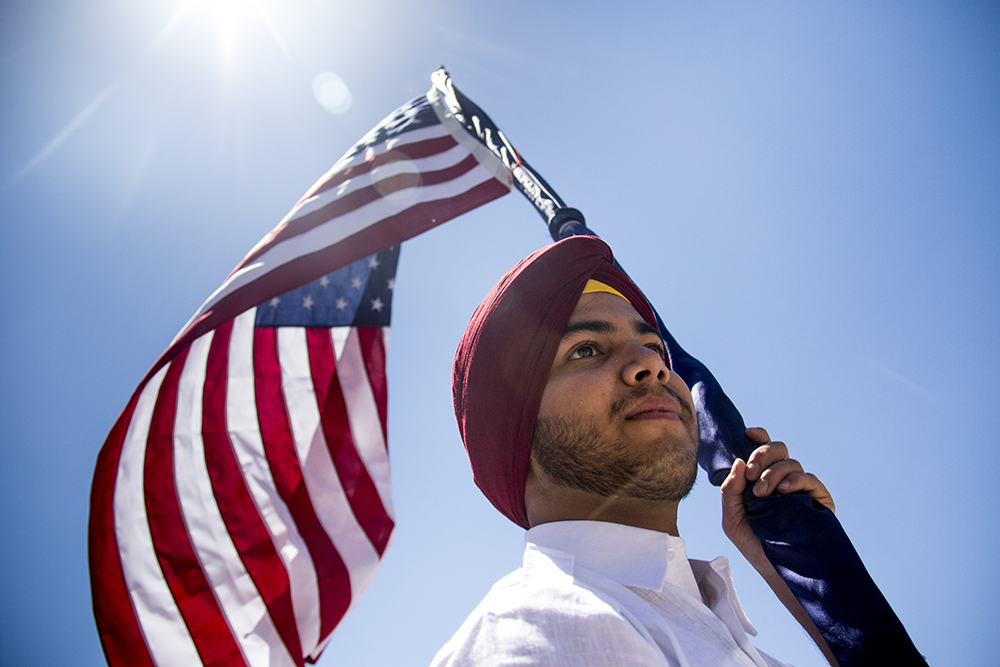 Karanpreet Singh holds up an American flag. The second-annual Sikh festival at East High School, May 28, 2017. (Kevin J. Beaty/Denverite)  sikh; colorado singh sabha; east high school; denver; colorado; parade; kevinjbeaty; denverite;