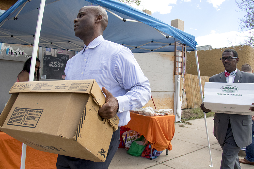Brother Jeff Fard and Christopher X carry boxes of food to be distributed to the community, May 13, 2017. (Kevin J. Beaty/Denverite)  brother jeff's cultural center; five points; mother's day; kevinjbeaty; denver; denverite; colorado;