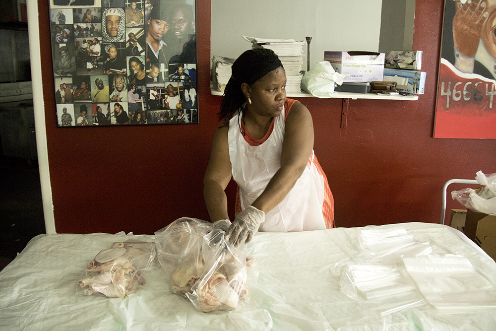 Regina Jones packs chicken into bags for distribution. Brother Jeff's Cultural Center in Five Points, May 13, 2017. (Kevin J. Beaty/Denverite)  brother jeff's cultural center; five points; mother's day; kevinjbeaty; denver; denverite; colorado;