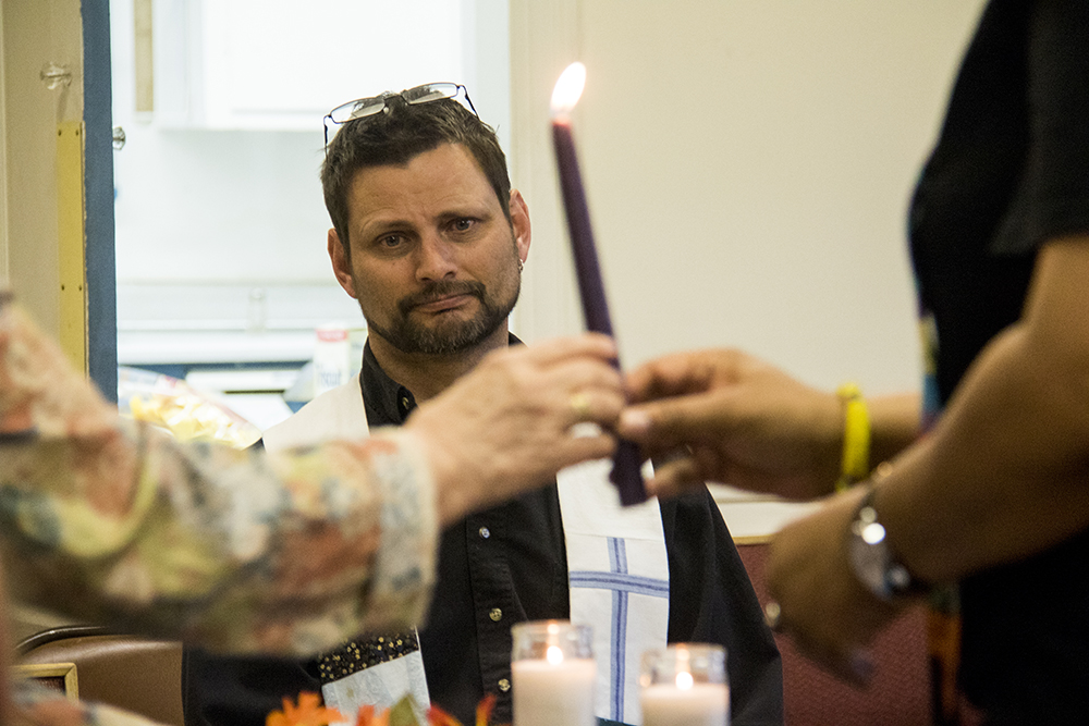 United Methodist UCC pastor Todd Smiedendorf watches a candle being lit during a Good Friday vigil for Ingrid Encalada Latorre, April 15, 2017. (Kevin J. Beaty/Denverite)  immigration; undocumented; deportation; kevinjbeaty; denver; colorado; mountain view friends meeting;