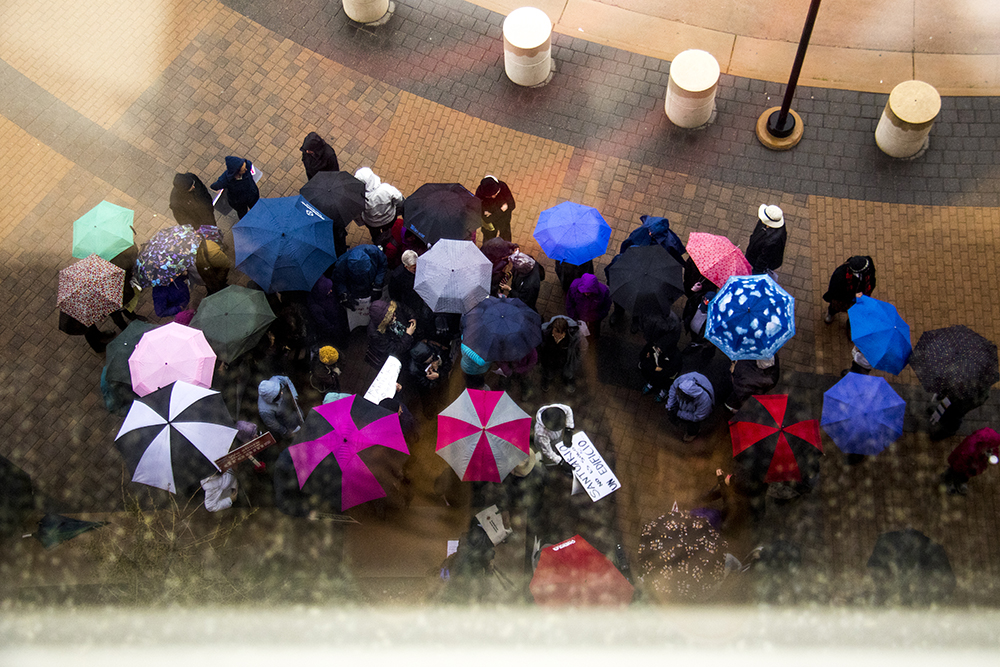 Supporters under umbrellas gather outside the Jefferson County Courthouse as Ingrid Encalada Latorre leaves sanctuary to go to court, May 3, 2017. (Kevin J. Beaty/Denverite)  immigration; undocumented; deportation; law; court; jefferson county; golden; colorado; kevinjbeaty; cowx; weather; umbrellas; rain;