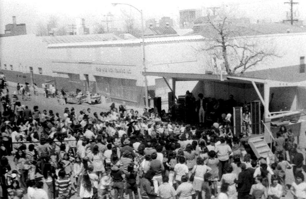 A crowd gathers at a covered stage to hear music during the Cinco de Mayo festival hosted by the West Side Coalition on Santa Fe Drive, 1973. (Denver Public Library/Western History Collection/)  archive; denver public library; history; cinco de mayo; chicano; santa fe drive; denverite; denver; colorado;