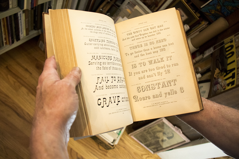 Tom Parson holds the Handy-Book of Printing Types, a cataloge of pre-digital fonts from 1901. Many of those typefaces no longer exist. May 4, 2017. (Kevin J. Beaty/Denverite)