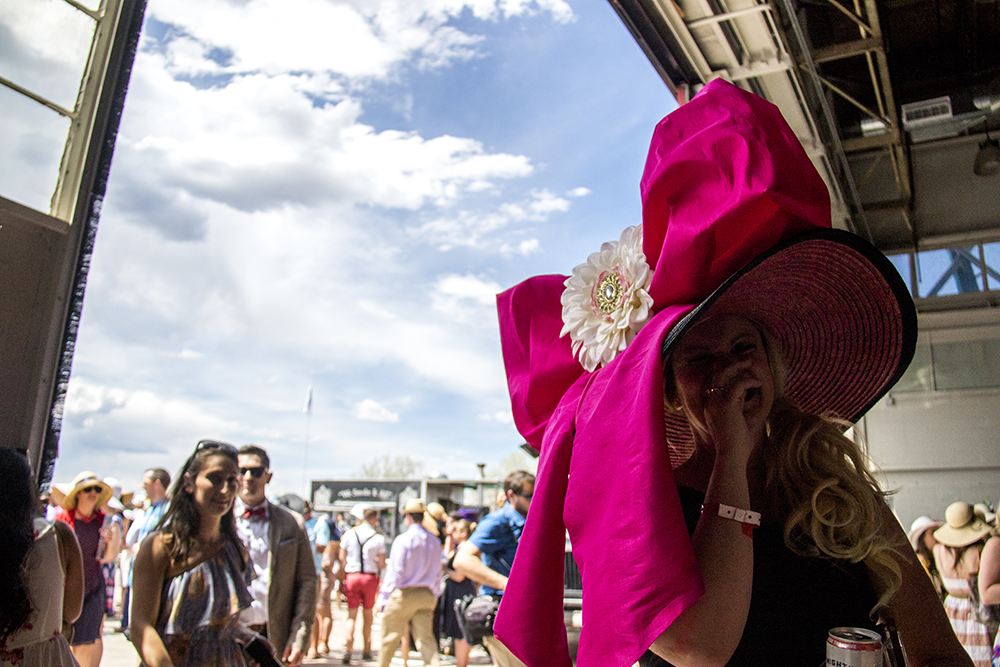 """Cindy Pick and her large pink-bowed hat. """"It's amazing what hot glue will do."""" A Kentucky Derby party at Stanley Marketplace, May 6, 2017. (Kevin J. Beaty/Denverite)  stanley marketplace; kentucky derby; aurora; kevinjbeaty; denverite; colorado;"""
